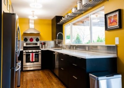 Modern kitchen with stainless steel appliances, yellow painted walls, and large replacement windows above kitchen sink