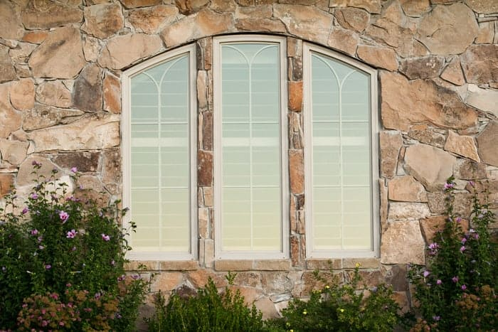 Three arched house windows installed in wall with stone veneer