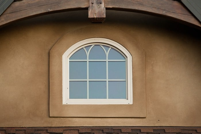 Arched house window placed above front entry of home