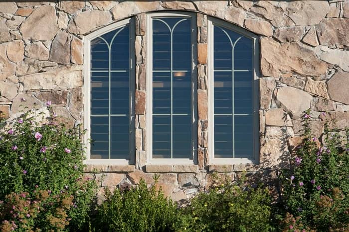 Three arched house windows set in wall with stone veneer