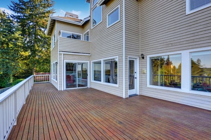 Vinyl windows and glass doors on house look out to wooden deck