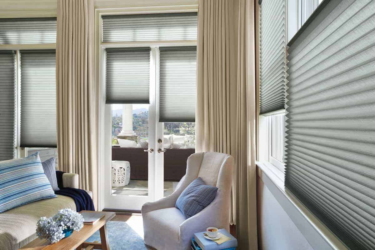 Window shades covering multiple windows in a home's living room