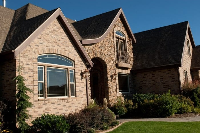 Brick and stone luxury home with new replacements windows looking out to front yard