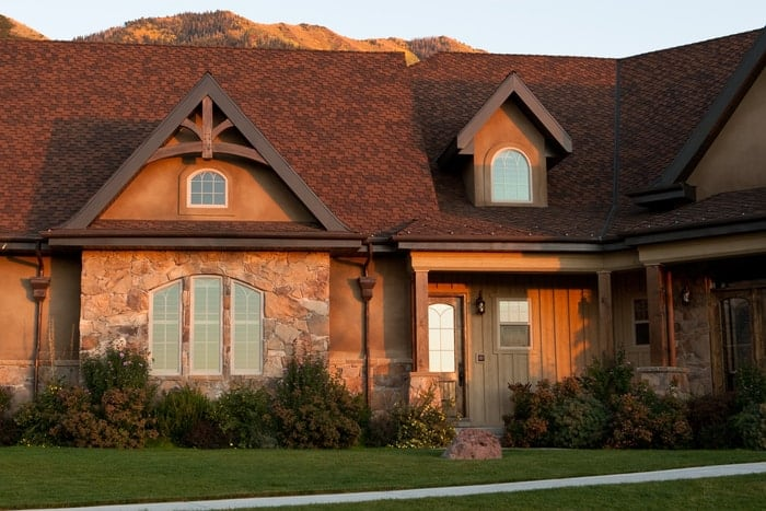 Setting sun illuminates luxury Utah home and its new house windows and front entry home door