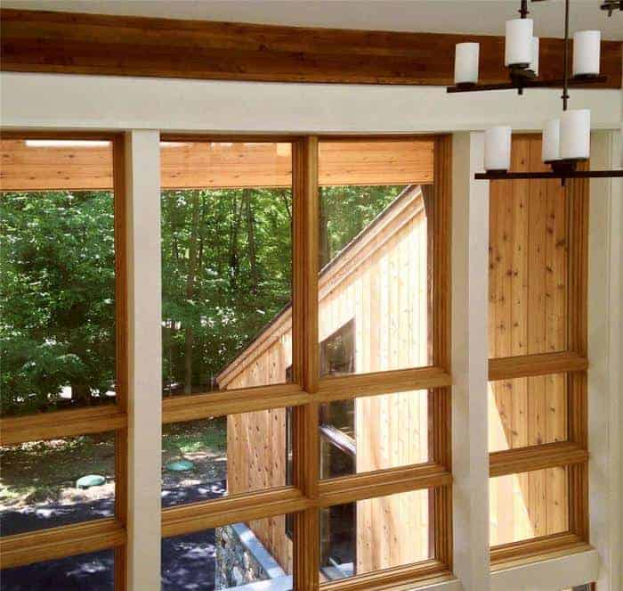 Tall wood windows look out to forest landscape in cabin