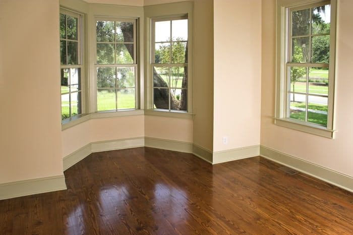 Bay wood window in unfurnished bedroom has view to trees outside