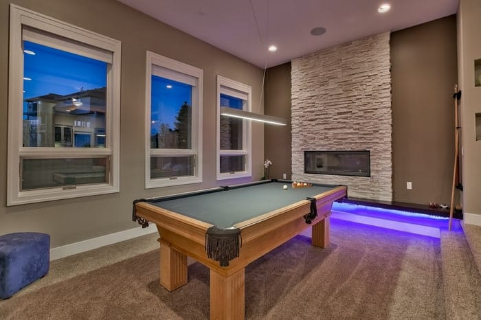 Windows line wall in room with billiards table