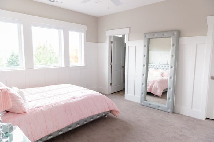 Windows give light to bedroom with tall wainscoting and light grey wall paint