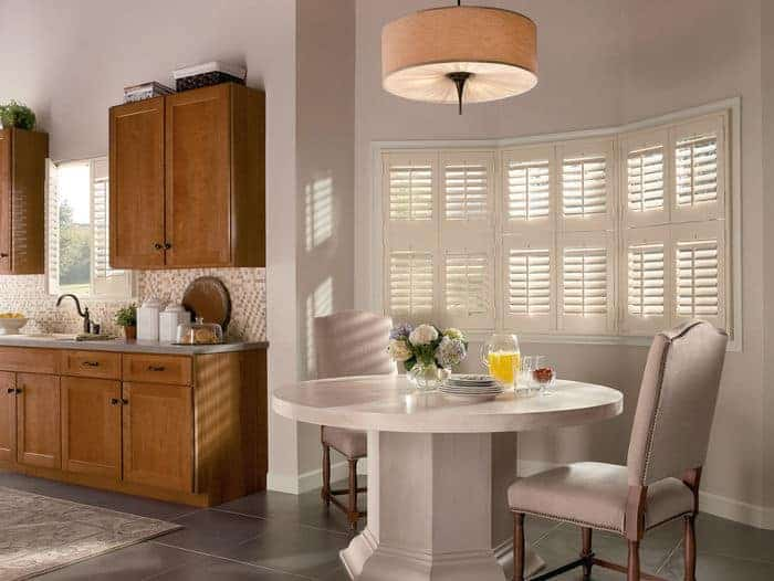 Vinyl window shutters filter in light from windows into kitchen and dining area