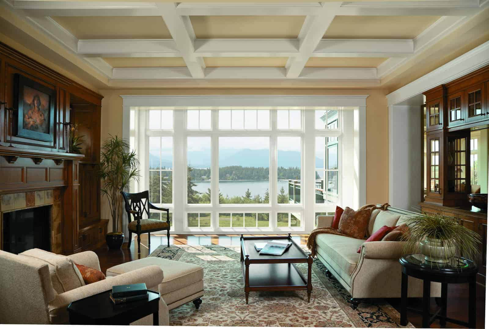 Large wooden windows overlook lake at mountain home