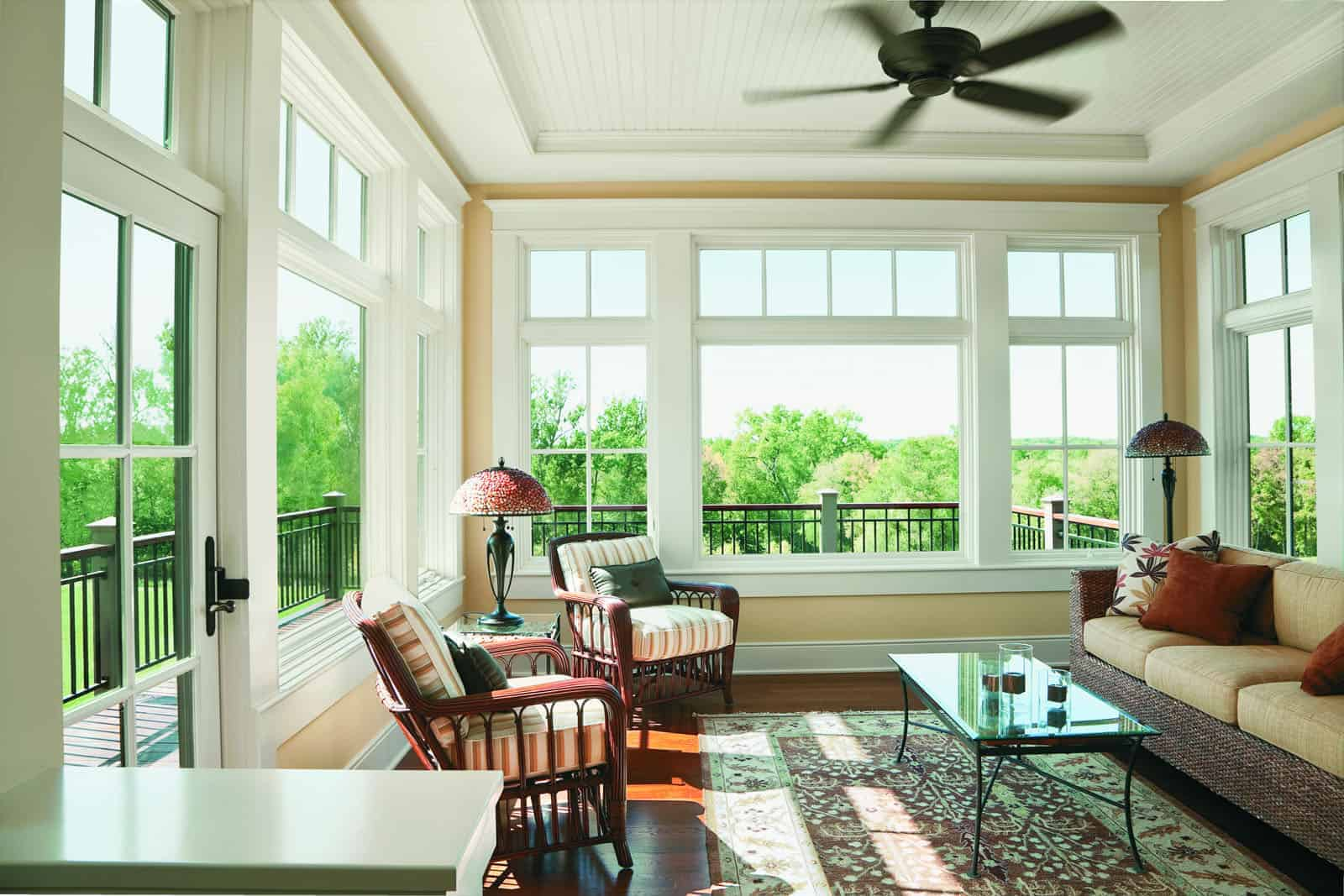 Wood windows line walls of residential home's sunroom