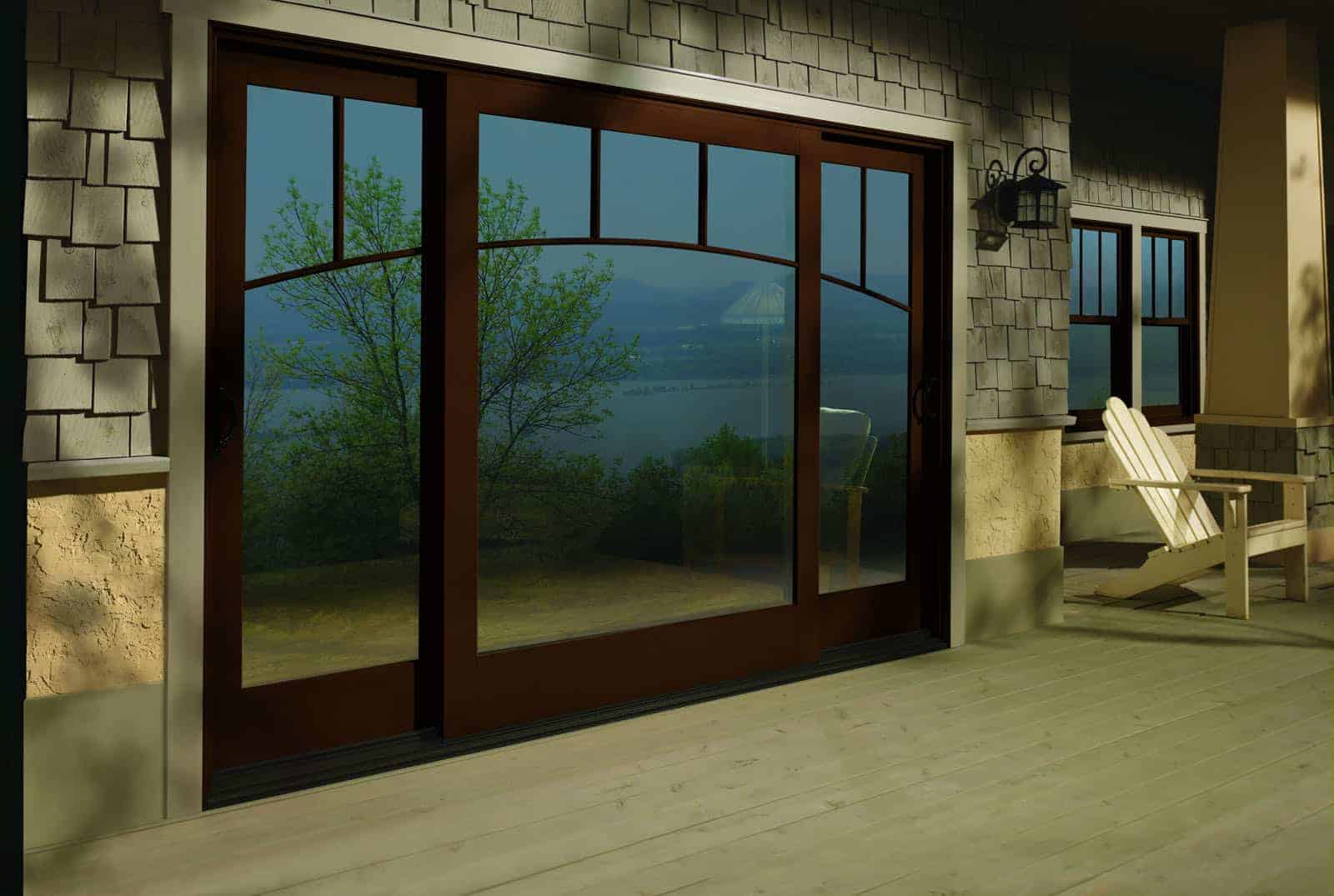 Wooden windows and wood clad sliding patio doors lead out to deck